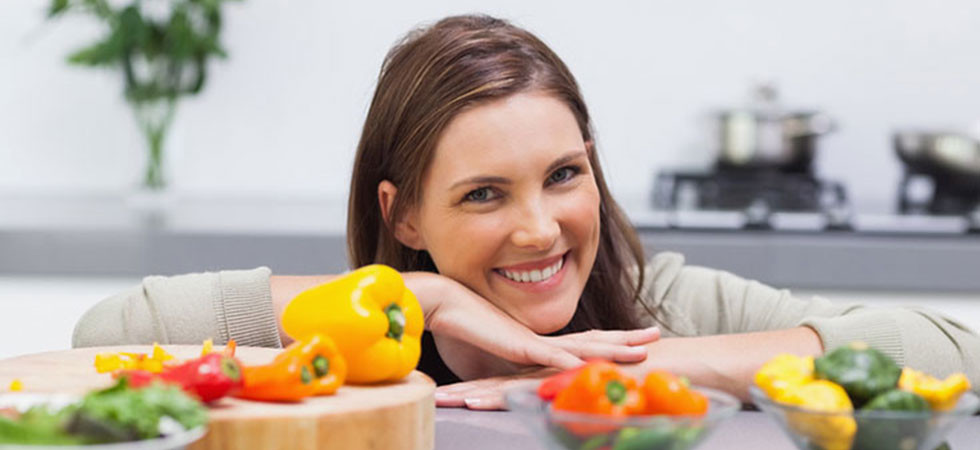 cheerful-woman-leaning-on-the-counter-of-her-kitchen