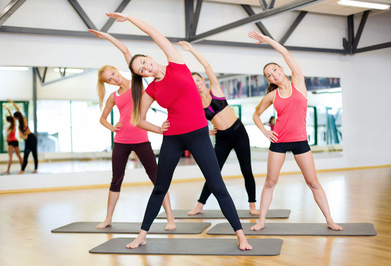 smiling-women-stretching-in-the-gym